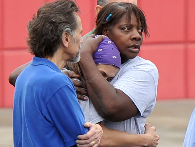 FedEx employee Lisa Aiken is embraced by a co-worker as other employees gather at a skating rink following a shooting at the FedEx facility on April 29 in Kennesaw, Ga. A gunman armed with an assault rifle opened fire and wounded six people before killing himself.