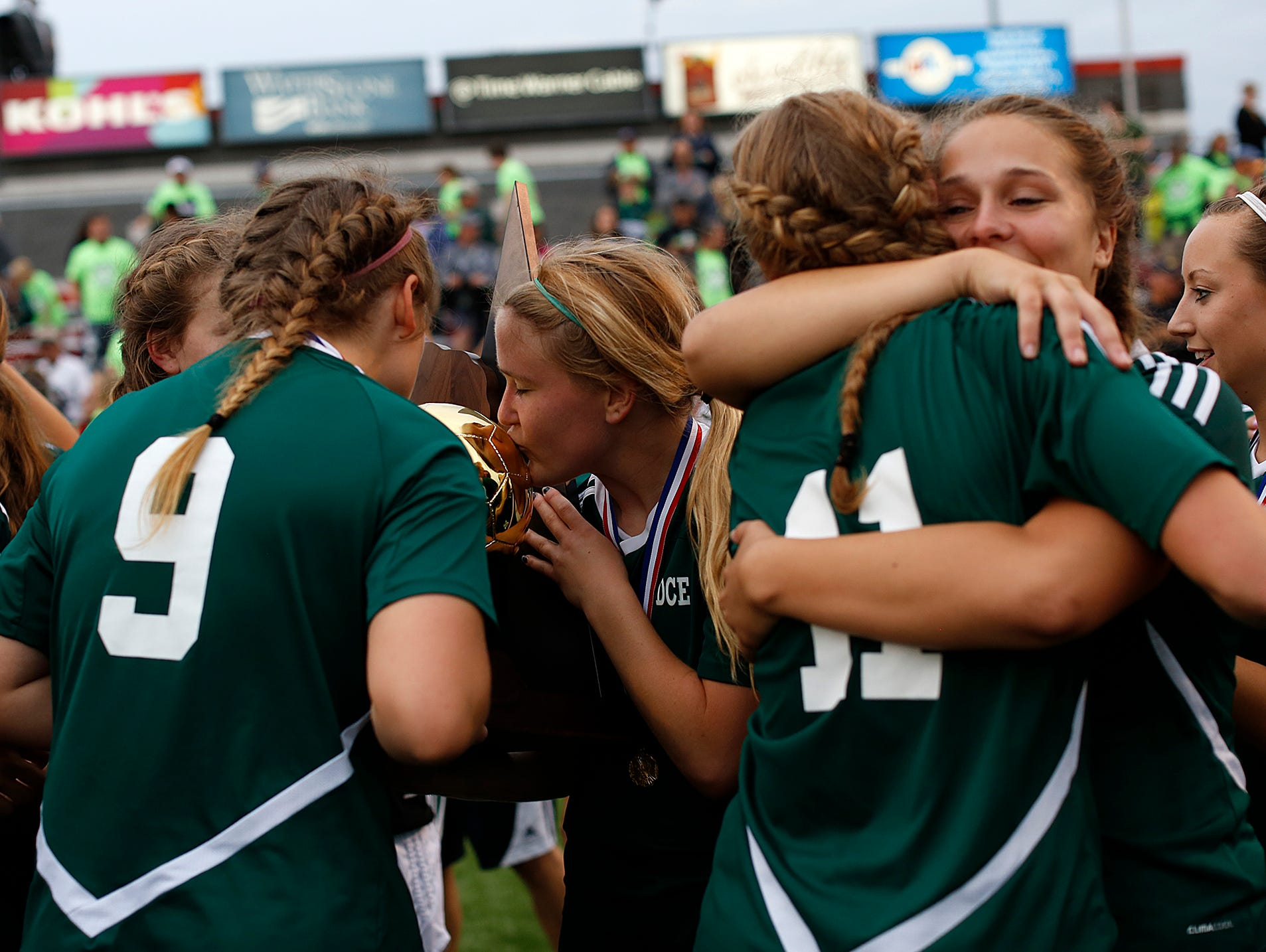 D.C. Everest players celebrate with the championship trophy after the Evergreens defeated Kettle Moraine in overtime during Saturday's Division 1 championship game in the WIAA state girls soccer tournament at Uihlein Soccer Park in Milwaukee.