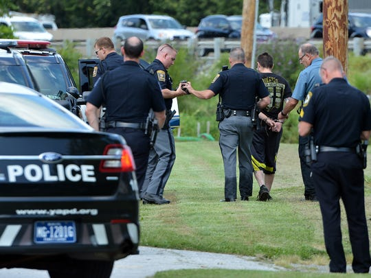 Police take a man into custody following a multi-agency search along Interstate 83 in Springettsbury and Spring Garden Townships, Thursday, August 24, 2017. The burglary suspect was arrested along Mill Creek behind the York Area United Fire Station. John A. Pavoncello photo