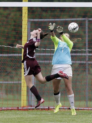 New Holstein's Shelly Van Grinsven, left, heads a ball toward Ozaukee goalkeeper Autumn Smith (1) during Saturday's WIAA Division 4 sectional final in New Holstein.