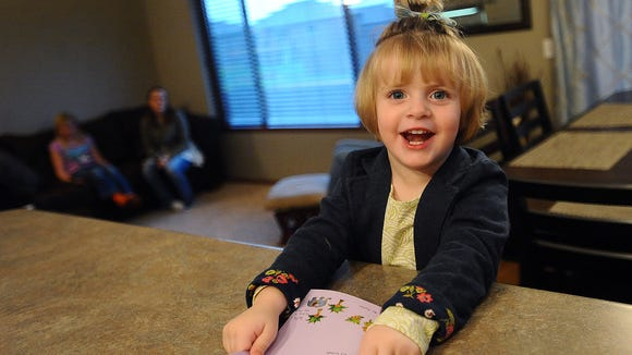 Reese Whitney, 2, reads a card at her home in southwest Sioux Falls on Wed., Oct. 22, 2014. Reese was diagnosed with anaplastic ependymoma grade 3 on May 24, 2013. She is being treated through St. Judes in Memphis, TN. Reese will be turning three on Nov. 28.
