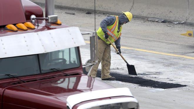 Road workers repair the surface on eastbound Interstate 696 between Ryan and Merideth in Warren on Friday afternoon.