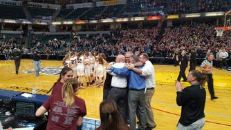 Central Noble players celebrate on the court and coaches celebrate in the foreground Saturday in the Class 2A state title game at Bankers Life Fieldhouse.