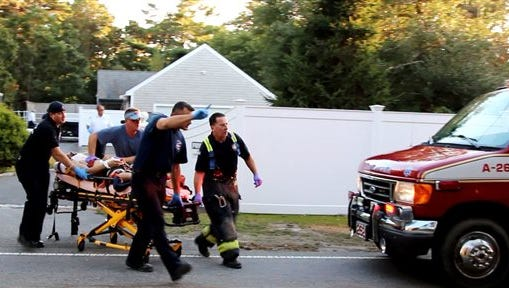 In this image taken from video provided by HyannisNews.com, a person is brought to an ambulance following a skydiving accident Sunday, in Barnstable, Mass. Barnstable police say the skydiving instructor and student died shortly after the crash near the Cape Cod Airfield.