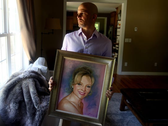 Jonathan Russo holds a portrait of his mother, Connie