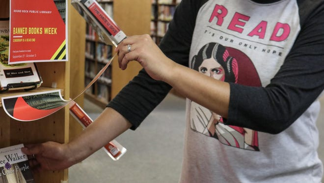 Round Rock Library employee Emily Jones checks out the Banned Books display.