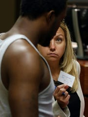 Assistant Public Advocate Melanie Lowe lets one of her clients know the date of his next appearance in court. Aug. 13, 2015