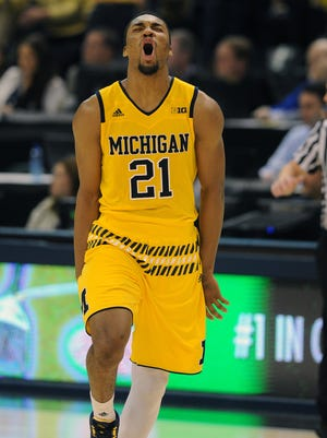 Michigan guard Zak Irvin (21) reacts after making the game-winning shot in the Big Ten tournament Thursday, March 10, 2016, at Bankers Life Fieldhouse in Indianapolis. Michigan won, 72-70, in overtime.