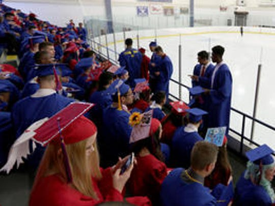 Graduates assemble in the stands as ice skaters practice