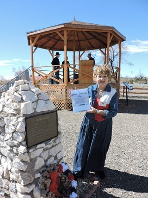 Patricia Kiddney, president of the Concordia Heritage Association in El Paso, Texas, was one of the speakers at the Columbus Historical Society's annual memorial service to honor the 18 U.S. citizens who died in the Pancho Villa raid of March 9, 1916.  She displays a photo of the memorial headstone that the Association purchased for the previously unmarked grave of W.A. Davidson, a victim of the Pancho Villa raid on Columbus in 1916.