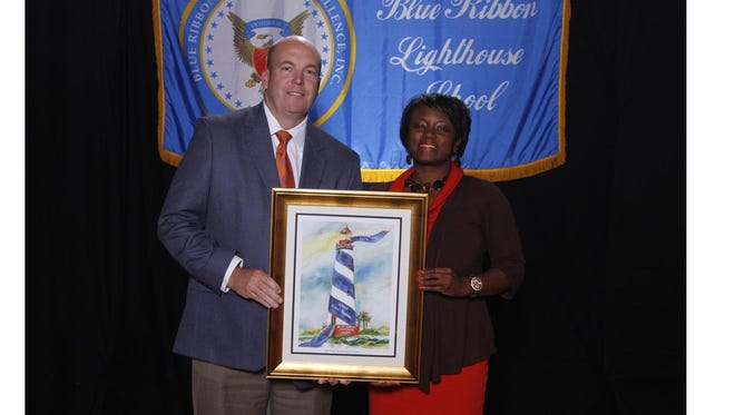 Shown posing with the Blue Ribbon Lighthouse School Award presented to Wren High School from left are Assistant Principal Chris Chapman and Principal Nichole Boseman.