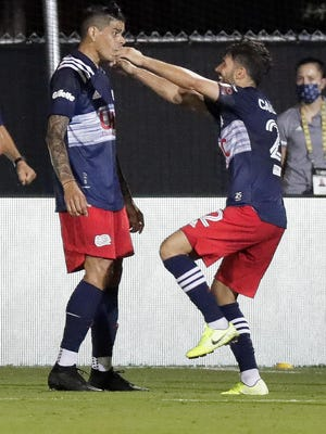 Moments after New England Revolution's Gustavo Bou, left, scored a goal against the Montreal Impact teammate Carles Gil jumps in his arms during the second half of an MLS match Thursday in Kissimmee.