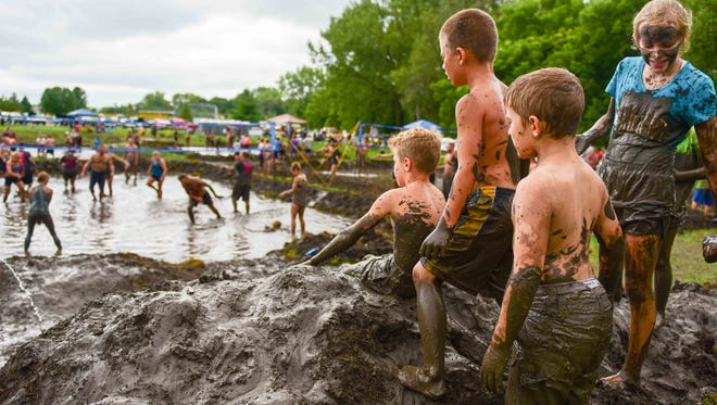 """Kids stand on what they call """"Mud Mountain"""" and watch the adults play mud volleyball on Saturday, August 29, 2015, during Altoona Palooza at  Sam Wise Youth Complex."""