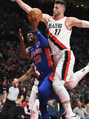 Detroit Pistons forward James Ennis III is fouled as he drives to the basket on Portland Trail Blazers center Jusuf Nurkic during the first half of an NBA basketball game in Portland, Ore., Saturday, March 17, 2018.