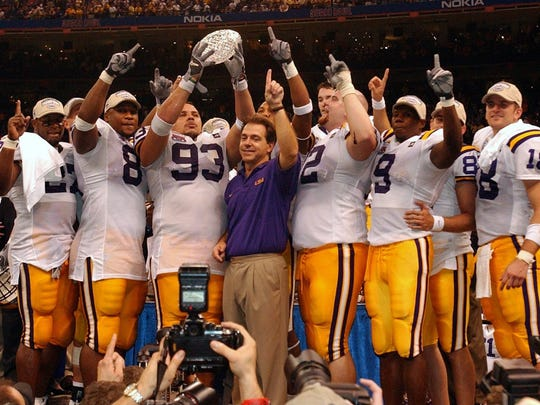 Louisiana State University coach Nick Saban is surrounded by his players as they hold up the National Championship Trophy following their 21-14 victory over Oklahoma in the Nokia Sugar Bowl at the Superdome in New Orleans, Louisiana, on Jan. 4, 2004.