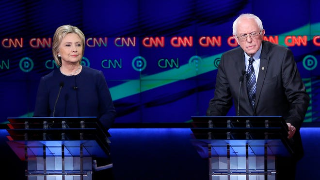 Democratic presidential candidates, Sen. Bernie Sanders, I-Vt., right, and Hillary Clinton listen to a question during a Democratic presidential primary debate at the University of Michigan-Flint, Sunday, March 6, 2016, in Flint.