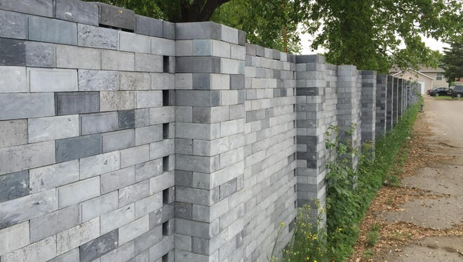 The wall separating Python's Recycling and the train tracks and surrounding neighborhood on St. Cloud's northeast side is made of plastic, interlocking bricks. The concept is similar to Lego toys and the bricks themselves were once produced by a former owner at Python's.