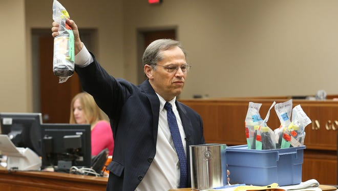 Second Assistant District Attorney Timothy Prosperi holds up a bottle of acid as evidence during the prosecution's closing arguments in the Rideout murder case Tuesday.