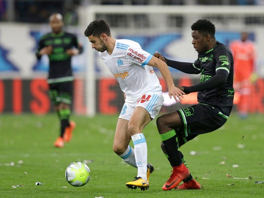 Marseille's Morgan Sanson, left, challenges for the ball with Guingamp's Felix Eboa Eboa, during the League One soccer match between Marseille and Guingamp, at the Velodrome stadium, in Marseille, southern France, Sunday , Nov. 26, 2017.(AP Photo/Claude Paris)