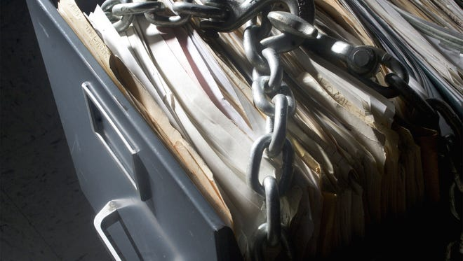 Photo illustration of a file cabinet that is chained shut.