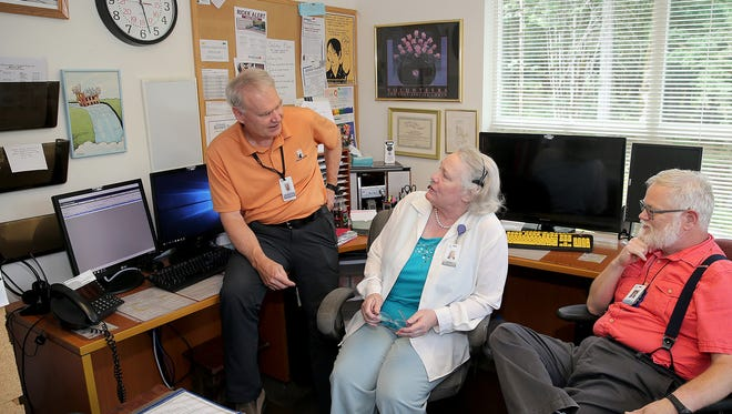 In this file photo, Kitsap Mental Health Services Crisis Clinic program manager Kelly Schwab, right, talks with Larry Tuke, left, crisis team volunteer, and Kristin Osman, center, a 2-1-1 operator in the crisis clinic space.