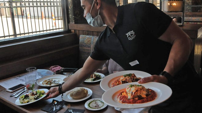 Evan Wheeler, YaYas Euro Bistro server, delivers plates of Bill's chicken and baked lasagna to a table during the soft opening on Friday. YaYa's will be opening up to the public on Monday, August 17.