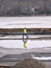 A worker on the shore of Pompton Lake in the first phase of the dredging work.