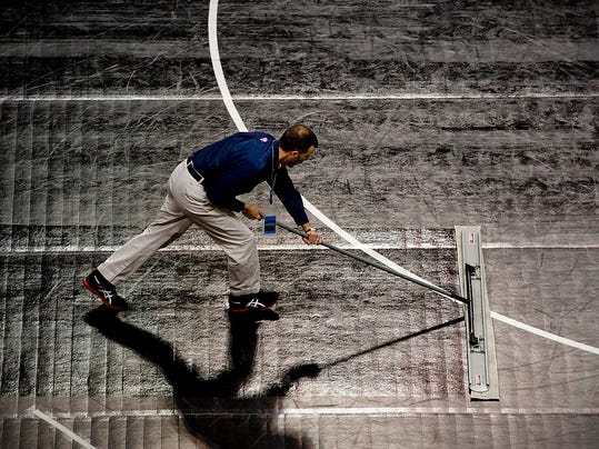 A PIAA official uses a mop to sanitize the mats between Class AA and AAA rounds at the Giant Center in Hershey, Pa., on March 7, 2013.