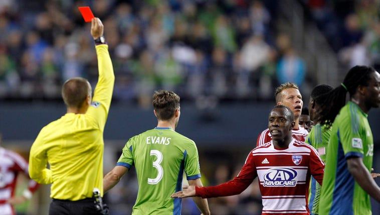 An MLS referee displays a red card.