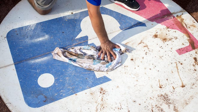 Texas Rangers groundskeeper George Carrillo, 40, wipes off the visitors' on-deck circle, which bears the Major League Baseball logo, before a baseball game against the Miami Marlins, Monday, July 24, 2017, in Arlington, Texas. Miami won 4-0.