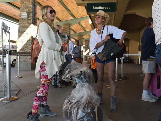 Covered with playa dust, Brielle Gearson, left, and Dina Nadezhdina wait to check-in for their flight home to Los Angeles Monday morning. Their baggage is wrapped in mandatory plastic because the playa dust can clog the conveyor system. An estimated 17,000 Burners utilized the airport from 30 countries, making it the largest single-event driver of traffic at R-TI.