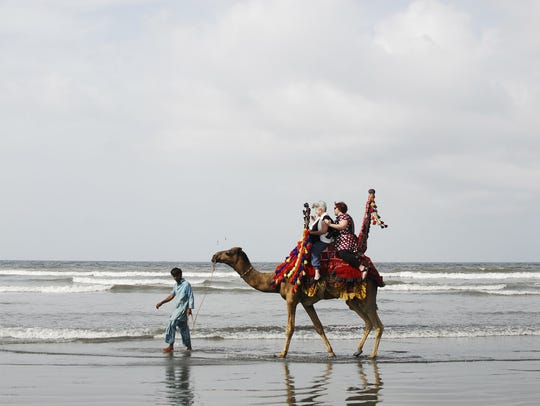 Abbey Doyle rides a camel in Pakistan.