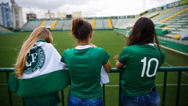Fans of Chapecoense gather at the Arena Conda to mourn following a plane crash that killed 76 people.