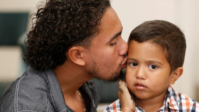 Roger Ardino gives his son Roger Ardino Jr. a kiss shortly after speaking to reporters at a news conference at the Annunciation House in El Paso, Texas, on Wednesday. Ardino and Pablo Ortiz, 28, and his son Andres spoke to the media about their experiences while being detained and separated for several months from their sons.