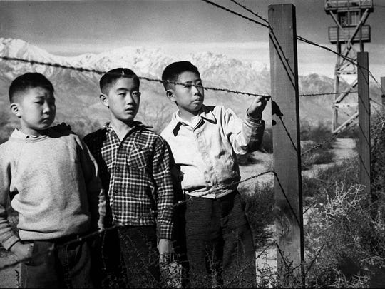 Children stand behind barbed wire at the Manzanar internment