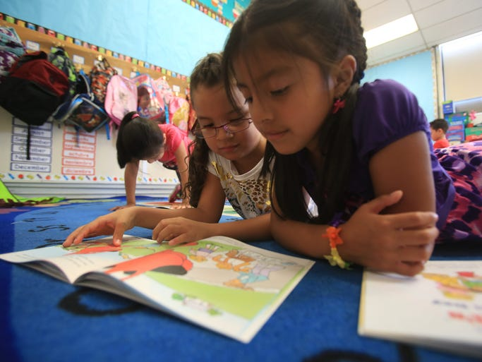 From left, first graders Emily Piedra and Nayeli Belezaca read books in class on the first day of school at the Carl L. Dixson Primary School in Elmsford on Sept. 2, 2014.