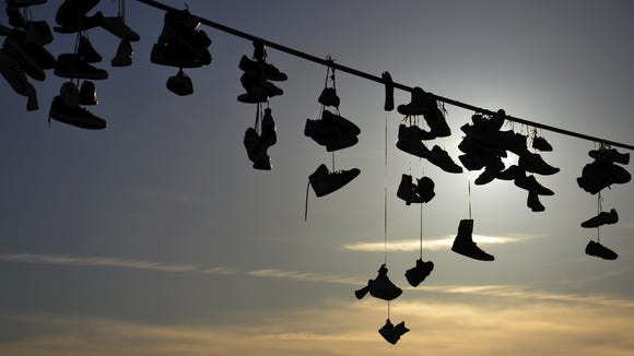 Shoes hanging from a wire.