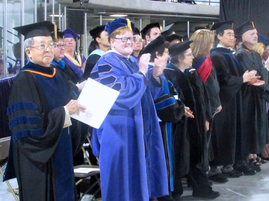 Elmira College faculty members applaud the class of 2016 at the start of Sunday's annual commencement exercise.