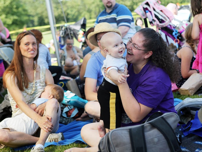 Carolyn Wallace bounces her six-month-old Garoin after the Latch On. More than one hundred participants at Family Building Blocks at Riverfront Park join the world record attempt for most babies breastfeeding at once in the Big Latch On.