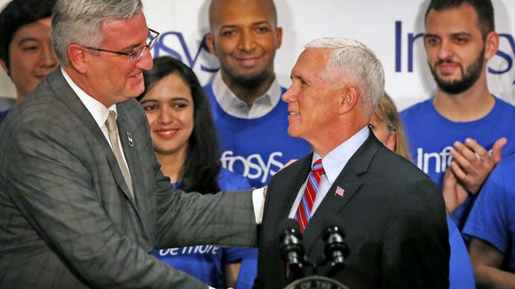Governor Eric Holcomb, left, shakes hands with Vice President Mike Pence after introducing him to speak during the Infosys announcement event, Thursday, April 26, 2018.  Infosys announced plans to build a U.S. education center as part of a $245 million campus near the Indianapolis International Airport, providing up to 3000 jobs.