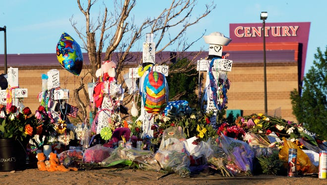 "In this July 27, 2012 file photo, crosses, flowers and other mementos of the victims of the Aurora, Colo. movie theater shooting are shown at sunrise with the movie theater in the background. Jury selection begins Tuesday, Jan. 20, 2015, in the trial of accused gunman James Holmes in the shootings at the Denver-area movie theater showing ""The Dark Knight Rises"" that left 12 dead and 70 wounded. Prosecutors are seeking the death penalty. Holmes pleaded not guilty by reason of insanity. His attorneys have acknowledged he was the gunman but say he is mentally ill and was gripped by a psychotic episode when he opened fire in the theater."