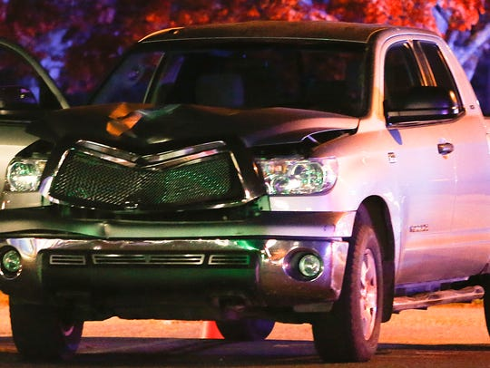 A pickup truck rests at the scene of an accident involving