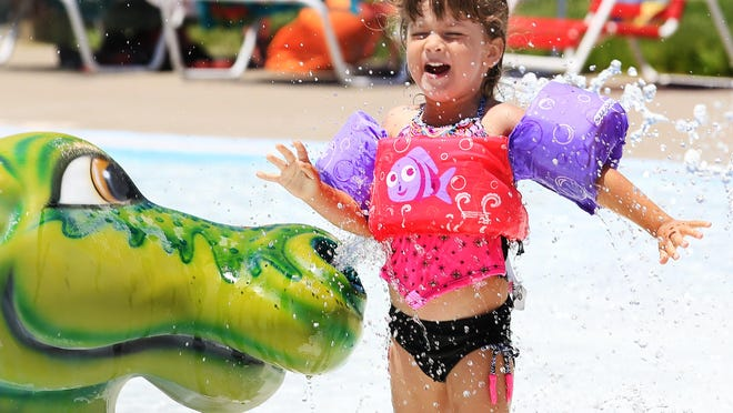 Isabella Yoder, 4, is surprised as she passes through the dinosaur water spray at Salt City Splash on Sunday afternoon. Close to 200 people entered the pool in the first hour it was open Sunday. Normally pools open on Memorial Day but this year the opening was pushed back because of the coronavirus pandemic. All pool staff are questioned on every shift to make sure they are healthy and have not been exposed to people who have tested positive for the coronavirus.