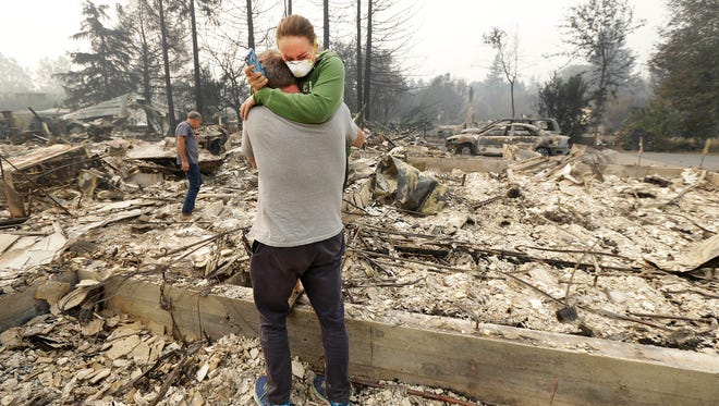 Todd Caughey hugs his daughter, Ella, on Tuesday, Oct. 10, 2017, as they visit the site of their home destroyed by fires in Kenwood, Calif.