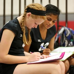 Getting in some homework during a varsity volleyball game are Plymouth freshman players Autumn Cannon (left) and Nirali Patel.