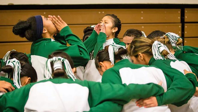 In this Feb. 2, 2016, photo provided by Richard Johnson, the girls basketball team at Flagstaff, Ariz., High School does a cheer with their hair tied back in traditional Navajo buns before taking the floor for pre-game warmups. But before play could begin the referee made them remove the hair ties, saying they were a safety hazard. This sparked sharp criticism from the school's principal and the president of the Navajo Nation. Officials say the hair ties won't be prohibited in the future.