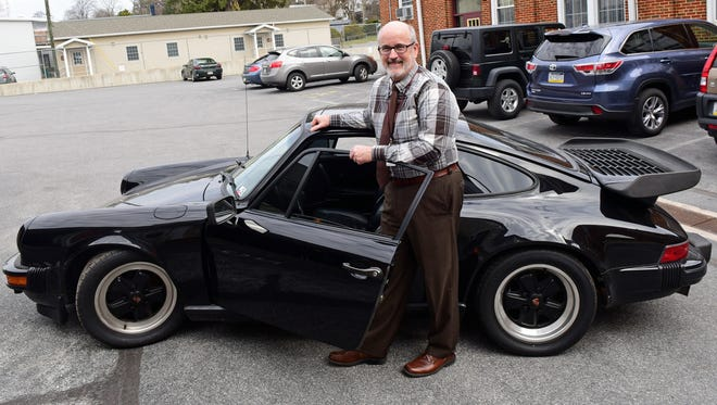 Principal Pat McDonald shows off the 1983 Porsche 911 that will be raffled at St. Andrew the Apostle Catholic School in Waynesboro. Ticket sales will help raise money for the school's capital campaign.