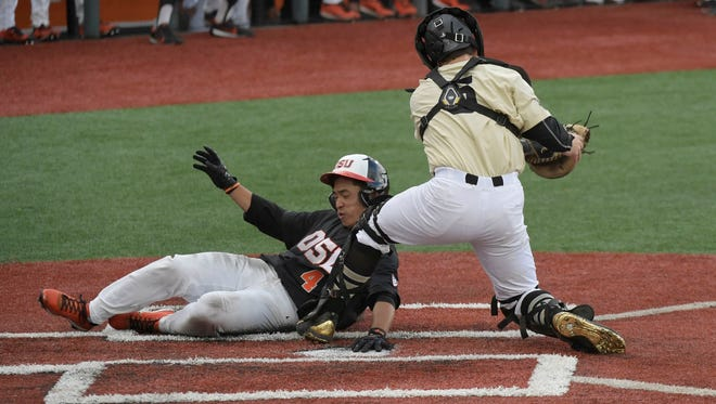 Oregon State's Stephen Kwan slides in to score in front of Vanderbilt catcher Jason Delay during Oregon State's 8-4 win in an NCAA college baseball tournament super regional game Friday, June 9, 2017, in Corvallis, Ore. (Mark YlenAlbany Democrat-Herald via AP)