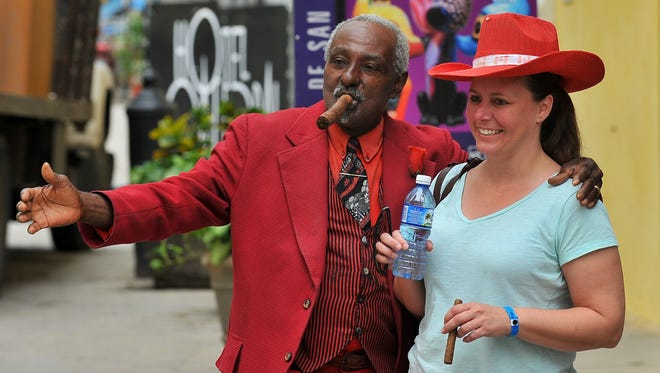 A tourist poses with a Cuban man as she visits the Old Havana, on December 16, 2015.