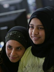 Eighth-grade students Reham Saihoot, right, and Amal